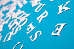 Letters. Background of letterson blue paper, shallow dof focus  on E Stock Photography