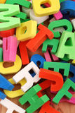Letters of the alphabet. Pile of colored letters of the alphabet on wooden table Royalty Free Stock Photos
