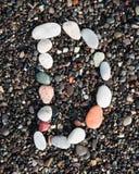 Letters alphabet laid on a black sand. D. English letters of alphabet laid on a black sand. D stock photo