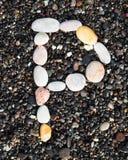 Letters alphabet laid on a black sand. P. English letters of alphabet laid on a black sand. P stock image