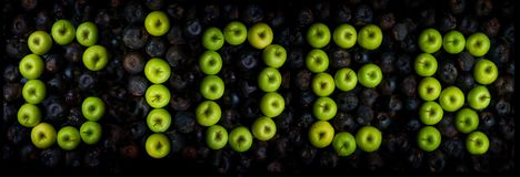 letters of the alphabet lined with green apples stock photo