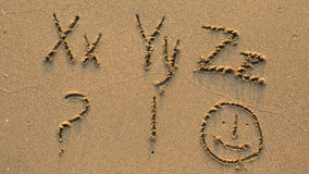Letters of the alphabet written on sandy beach Royalty Free Stock Photos