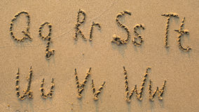 Letters of the alphabet written on sandy beach Stock Images
