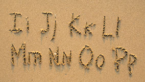 Letters of the alphabet written on sandy beach Royalty Free Stock Image