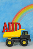The letters AUD, the symbol for the Australian dollar, in the ba. The letters AUD the symbol for the Australian dollar, in the back of a mining truck, against a stock images
