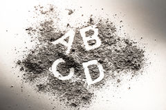 Letters a, b, c, and d written in grey ash, sand, filth or dust Stock Images