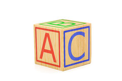 Letters A, B and C imprinted on sides of single brown wooden cub. E on white background stock photography