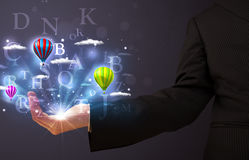 Letters and balloons in the hand of a businessman Stock Image