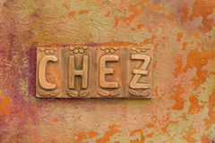 Letters `Chez` on orange background. Ornate letters `chez` on an orange painted wall at a restaurant in Corse, France stock photo