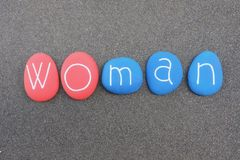 Woman and man in one word composed with red and blue painted stones over black volcanic sand Royalty Free Stock Photos