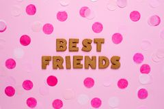 Letters cookies Best friends with confetti on pink background stock image