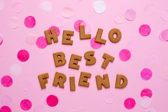 Letters cookies Helllo Best Friend with confetti on pink background royalty free stock images