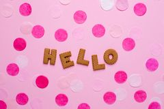 Letters cookies Hello with confetti on pink background stock images