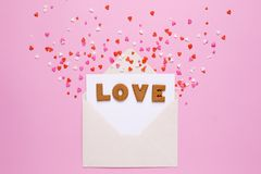 Letters cookies Love with envelope and red hearts on pink background royalty free stock images
