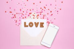 Letters cookies Love with envelope and red hearts on pink background stock images