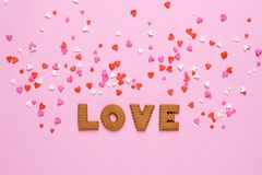 Letters cookies Love with pink and red hearts on pink background stock photography