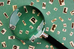 Letters cut from newspaper and magnifying glass Royalty Free Stock Images