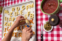Letters of dough with tomatoe sauce Royalty Free Stock Photography
