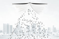 Letters fall from the book at city background Royalty Free Stock Image