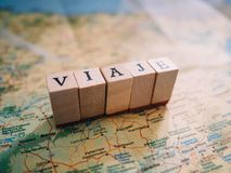Letters that form the word Travel in Spanish on top of a map royalty free stock photos