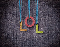 Letters hanging strings. Lol Letters hanging strings with blue sackcloth background Stock Photo