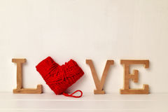 Letters and heart-shaped coil of yarn forming the word love Stock Image