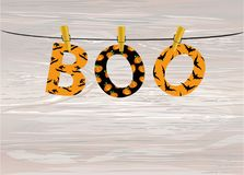 The letters and the inscription of a boo Halloween hang on cloth. Espins on a rope or string. Vector on wooden background. Festive garland. Greeting card or Stock Images
