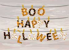 The letters and the inscription of a boo happy Halloween hang on. Clothespins on a rope or string. Vector on wooden background. Festive garland. Greeting card Stock Photography