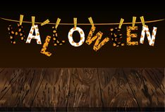 The letters and the inscription of a happy Halloween hang on clo. Thespins on a rope or string. Vector on wooden background. Festive garland. Greeting card or Stock Photo