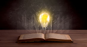 Letters and lightbulb over book Stock Photography