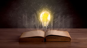 Letters and lightbulb over book Stock Images