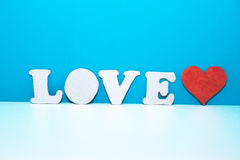Letters LOVE and red cardboard heart on white shelf Stock Photo