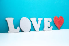 Letters LOVE and red cardboard heart on white shelf Stock Photos