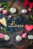 Letters LOVE on rustic background with hearts and flowers.  Stock Image
