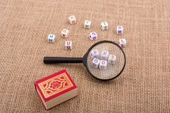 Letters, magnifying glass and the Holy Quran. Letter cubes, magnifying glass and the Holy Quran Stock Photo