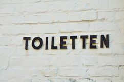Letters from metal. Point to a toilet Royalty Free Stock Photography