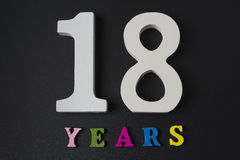 Letters and numbers for eighteen years on a black background. Royalty Free Stock Photography