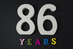 Letters and numbers eighty-six years old on a black background. Royalty Free Stock Photos