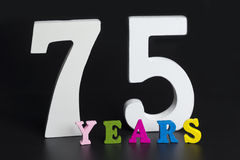 Letters and numbers-seventy-five on the black background. Stock Photo