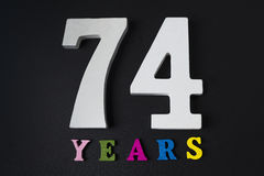 Letters and numbers seventy-four years on a black background. Stock Image