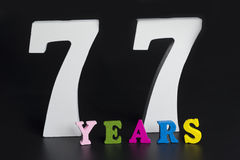 Letters and numbers-seventy-seven on a black background. Letters and numbers-seventy-seven on black isolated background Royalty Free Stock Image