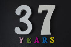 Letters and numbers thirty-seven years on a black background. Royalty Free Stock Photography