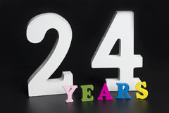 Letters and numbers twenty-four years on a black background. Stock Photos