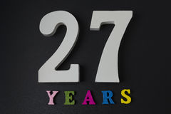 Letters and numbers twenty-seven years on a black background. Letters and numbers twenty-seven years on a black isolated background Stock Image