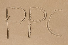 The letters P P C drawn in the sand Stock Photo