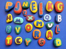 Letters pattern. Colorful letters painted on natural stone on blue background royalty free stock images