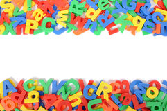 Letters of plastic toy alphabet border on white background, copy space Royalty Free Stock Photos