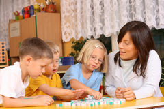 Letters and preschoolers. Teacher and 5-6 years old girl and boys learning with letters Stock Photography