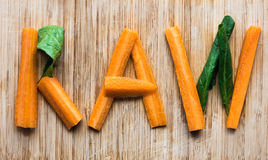 Letters of Raw - concept with vegetables. Eat raw concept with carrots, spinach stock photos
