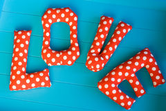 The letters with red polka dot fabric. LOVE on blue wooden background Stock Photo